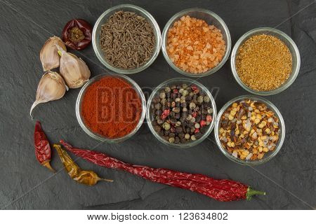 Various kinds of spices in glass bowls on a slate background. Preparation for cooking spicy food. Spices for master cook. The spice trade. Sale of spices in the kitchen.