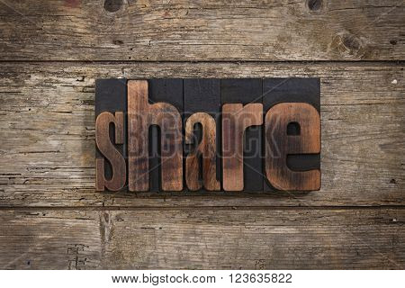 share, word set with antique letterpress type on rustic wooden background