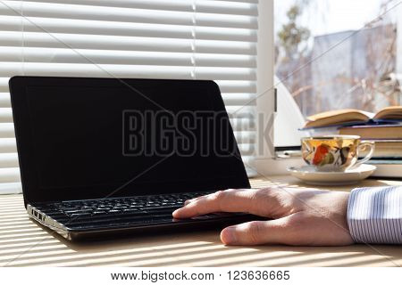 Man uses laptop on workstation. Corporation employees works from home. He contacts with the office through the Internet.