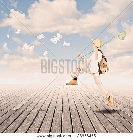 little explorer holding a butterfly net on a wharf