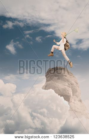 little explorer holding a butterfly net on a mountain