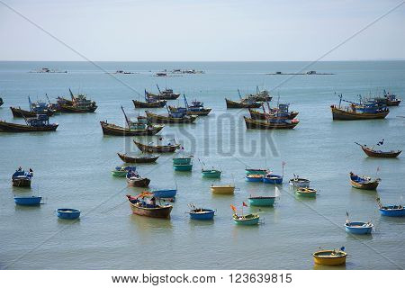 MUI NE, VIETNAM - DECEMBER 25, 2015: The South China sea covered with fishing boats. The fishing harbour of Mui Ne. Fishing boats waiting out at sea