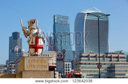 LONDON UK - SEPTEMBER 10, 2015 - City of London arm, Icon on the entry of City of London in front of London Bridge. Modern skyscrapers of financial district on the background