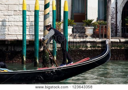 Venice, Italy - March 19, 2016: Traditional Gondolas at Venice Rialto main canal. The Gondola is a traditional, flat-bottomed Venetian rowing boat, well suited to the conditions of the Venetian lagoon