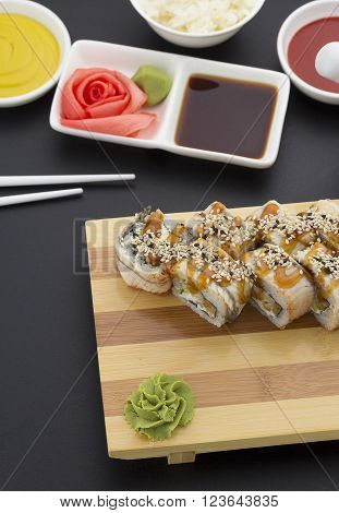 Japanese Cuisine. Eel Sushi Roll On A Wooden Plate With Ginger Wasabi Over Black Background