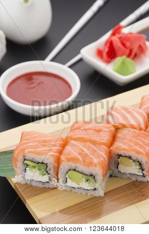 Salmon Sushi Roll On Wooden Plate ( Gete ) With Ginger Wasabi Chopsticks And Sauces Over Black Backg