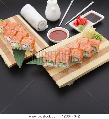 Salmon Sushi Roll On Bamboo List And Wooden Plate ( Gete ) With Ginger Wasabi Chopsticks And Sauces