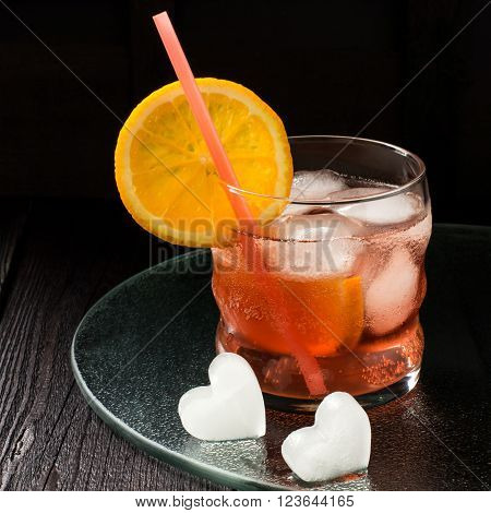 Aperitif aperol cocktail with orange slices and ice on a dark background. Square image