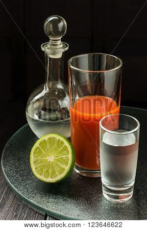 Ingredients for bloody mary cocktail: vodka in a decanter and a glass tomato juice in a highball on a glass tray