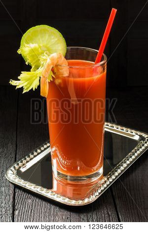 Bloody Mary cocktail with vodka and tomato juice garnished with lime celery and shrimp
