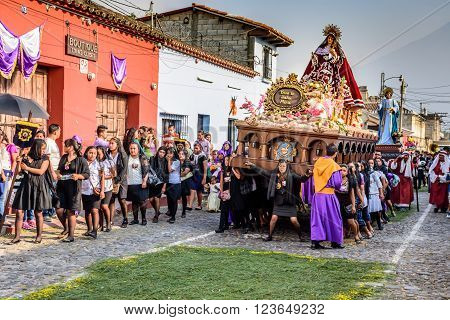 Antigua Guatemala - March 24 2016: Local women carry float with Virgin Mary in Holy Thursday procession in colonial town with most famous Holy Week celebrations in Latin America. Agua volcano behind.