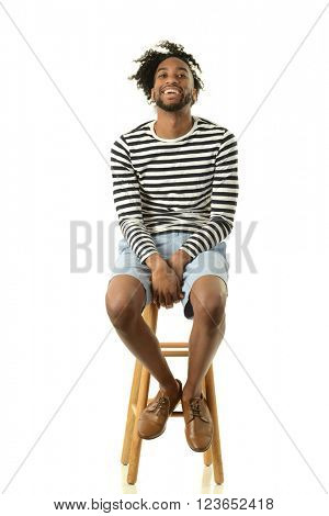 Young black man smiling seating isolated on a white background