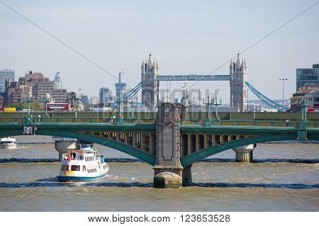 LONDON, UK - SEPTEMBER 10, 2015: City of London view from the river Thames, London bridge, tourist's boats and Tower bridge on the background