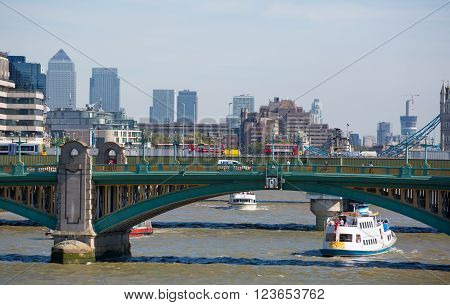 LONDON, UK - SEPTEMBER 10, 2015: City of London view from the river Thames, London bridge, tourist's boats and Canary Wharf on the background