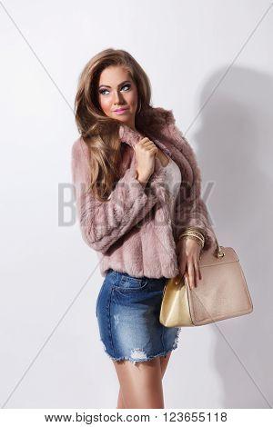 Attractive pretty rich woman posing in a fur coat
