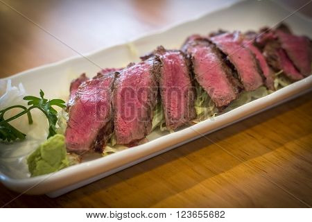 Japanese seared beef tataki served rare on bed of shredded lettuce