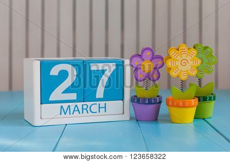 March 27th. Image of march 27 wooden color calendar on white background with flowers.  Spring day, empty space for text. World Theatre Day.