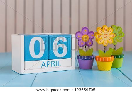 April 6th. Image of april 6 wooden color calendar on white background with flowers. Spring day, empty space for text.
