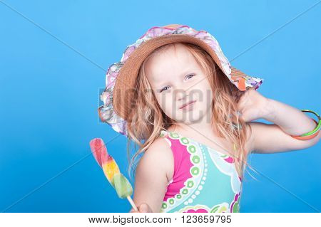 Smiling baby girl 4-5 year old eating ice cream in room over blue. Wearing hat and swim suit. Looking at camera.