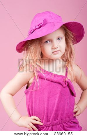 Stylish kid girl 4-5 year old wearing trendy suit and hat in room over pink. Looking at camera. Childhood. Summer time.