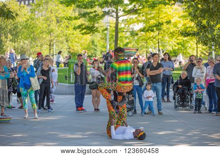 LONDON, UK - SEPTEMBER 10, 2015: Street performance by African's artists at south embankment of the River Thames. Lots of people watching the show at the background