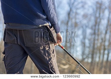 Close up rear view of man with fishing rod in early spring