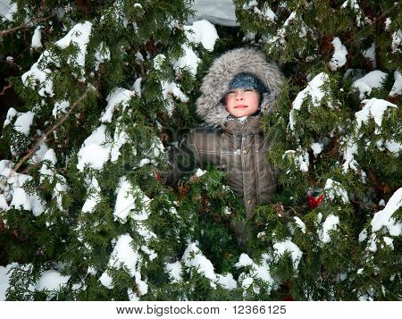 Young boy wearing winter jacket with furry hood playing outdoors