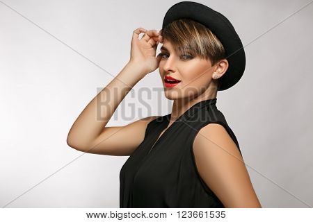 Close up of an attractive young  woman wearing black  t-shirt, silver pierced earrings and a fancy hat.