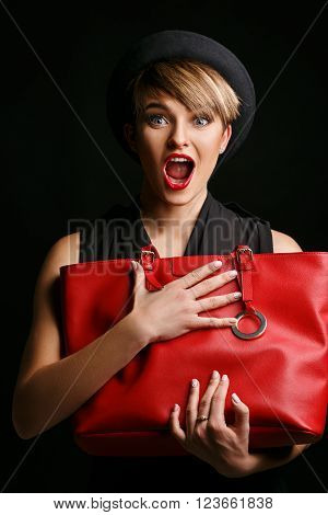 Close up of a beautiful  woman with a good sense of humor , holding her  fancy red bag.