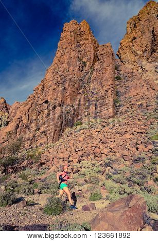 Woman cross country running in mountains on dirt path. Beauty female runner jogging and training with backpack outdoors in nature trail running on rocky trail footpath on Tenerife with rocky mountains in background Canary Islands.