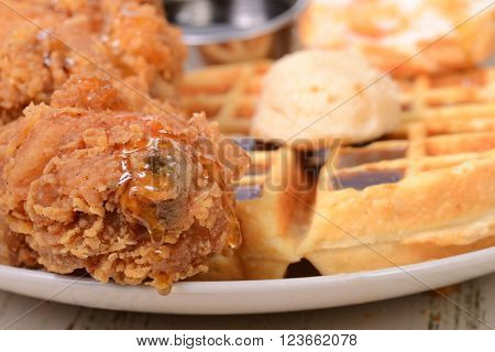 Closeup of Chicken and Waffles with honey, maple butter and maple syrup