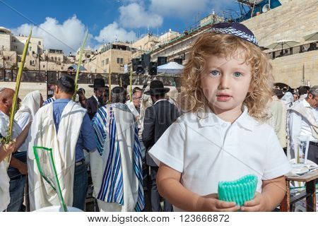 Cute little boy with long blond curls and blue eyes in blue skullcap. He stands at Western Wall of Temple. The Jewish holiday of Sukkot