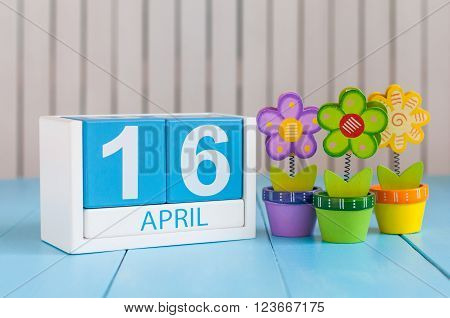 April 16th. Image of april 16 wooden color calendar on white background with flowers. Spring day, empty space for text.