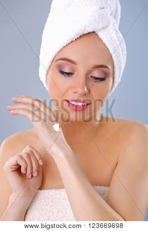 Young woman  putting cream on her hand Isolated on gray background.