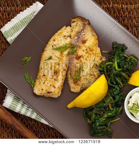 Baked Tilapia Fish with Sauteed Spinach. Selective focus.
