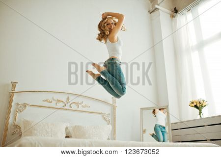 happy young woman jumping on the bed. young blonde woman jumping on the bed and raises his hands to the top. curly blonde jumping on the bed.Cheerful young woman jumping on the bed at home