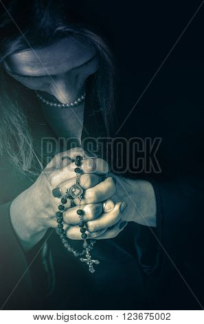 Closeup on a woman praying with a rosary on her hands