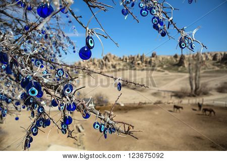 Naked tree with hanging decorations. Decorations are blue with image of the Fatima eye talisman. On the soft background there are horses, rock formation and the blue sky.