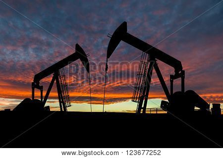Dramatic sky over two pumpjacks in rural Alberta Canada. These jacks can extract between 5 to 40 litres of crude oil and water emulsioin at each stroke.