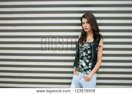 Young beautiful fashionable brunette woman in black leather jacket posing outdoors against urban style background of metal strips
