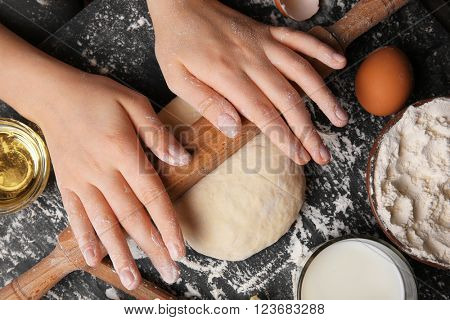 Female hands rolling out a dough, close up
