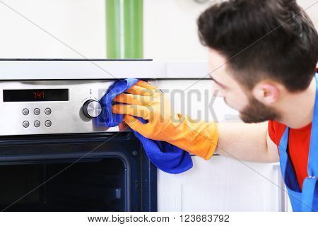 Man cleaning oven in the kitchen