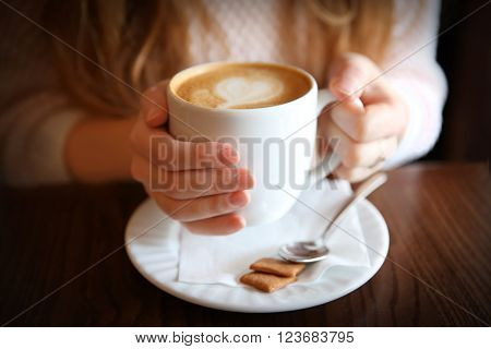 Woman with cup of cappuccino on table in cafe