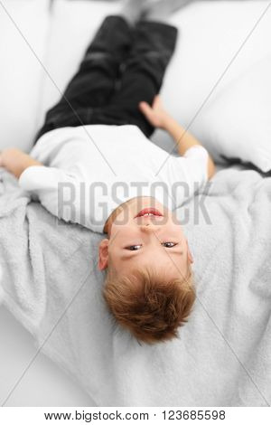 Portrait of cute cheerful boy lying upside down on sofa in the room
