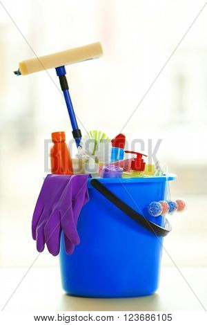 Cleaning set with products and tools in blue bucket