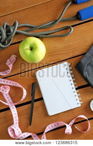 Athlete's set with equipment, notebook and apple on wooden background