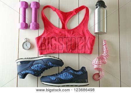 Athlete's set with female clothing, equipment and bottle of water on white wooden background