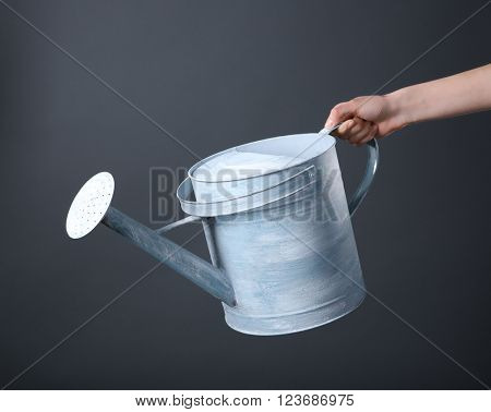 Female hand holding metal watering can on grey background