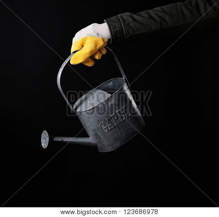 Hand holding metal watering can on black background