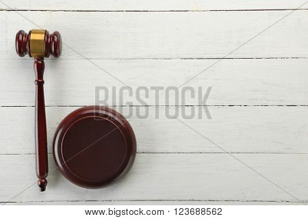 Gavel on wooden table, top view